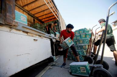 کارگران عراقی مشغول تخلیه بار کامیون حامل لوازم آرایشی وارداتی از ایران