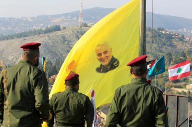 Lebanese Hezbollah forces with a banner showing Iranian general Qasem Soleimani. FILE