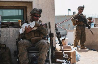 A US Marine holding a baby in Kabul airport. August 20, 2021