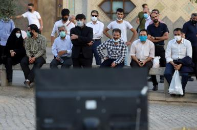 People watch the debate of presidential candidates at a park in Tehran, Iran June 12, 2021.