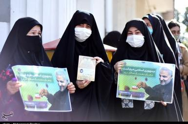 A group of women voters in segregated que holding posters of Qasem Soleimani killed by the US. June 18, 2021