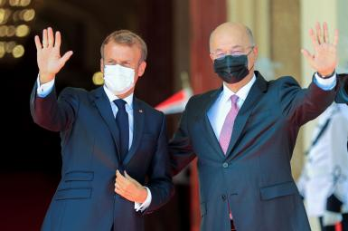 Iraq's President Barham Salih and France's President Emmanuel Macron gesture during a welcome ceremony ahead of the Baghdad summit. August 28, 2021.