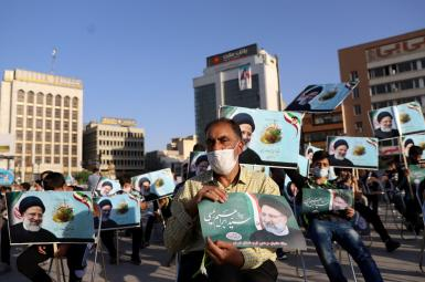 A supporter of  Ebrahim Raeesi holds a poster of him during an election rally in Tehran, June 14, 2021.