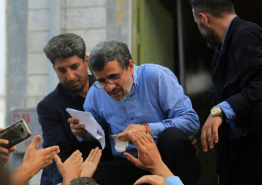 Iran's former president Mahmoud Ahmadinejad reading petitions during one his trips to regions. Undated