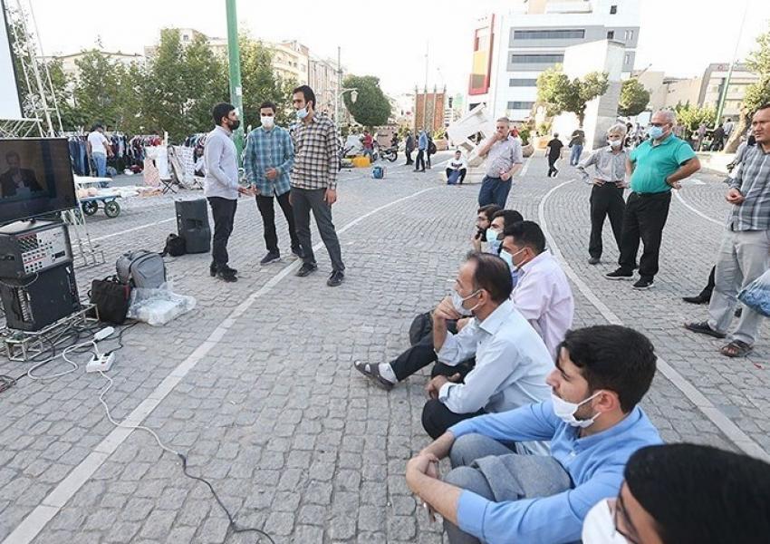 People in a Tehran street watching the second presidential debate. June 8, 2021